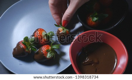 Woman's hand dips strawberry into chocolate mixture and puts it on the plate #1398318734