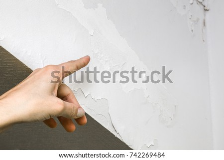 Woman's hand finger pointing to shabby wall defects near the roof window due to humidity problems.