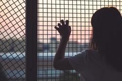 Woman's hand grabs the fence, concept of imprisonment, social issue and prostitution issue