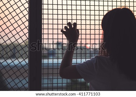 Woman's hand grabs the fence, concept of imprisonment, social issue and prostitution issue #411771103