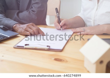 woman's hand hold ballpoint pen writing on  agreement paper sheet, fill in document template, applying for mortgage loan