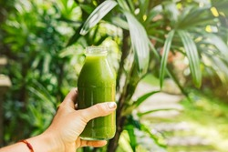 Woman's hand holding a bottle with green cold-pressed juice, nature background. Healthy eating, detoxing, juicing, fasting, body cleancing concept