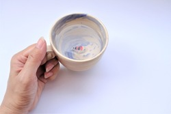 Woman's hand holding a ceramic cup that have water and little ceramic carp fish inside. Creative design oriental beauty and zen style.