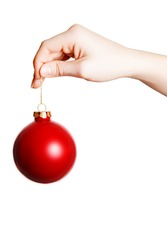 Woman's hand holding a Christmas ball on a white background