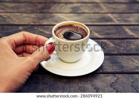 woman\'s hand holding a cup of Turkish coffee \