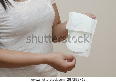woman\'s hand holding a daily sanitary pad.
