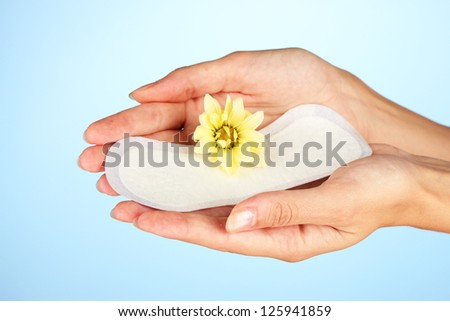 woman's hand holding a daily sanitary pad on blue background close-up