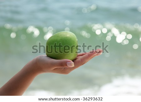 Woman`s hand holding a green apple on beautiful ocean background
