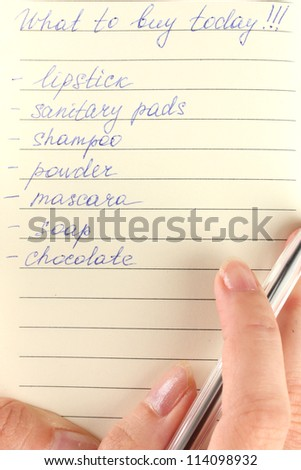 woman's hand holding a notebook with a shopping list close-up