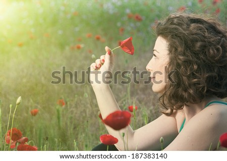 Woman\'s hand holding a poppy flower at evening sun , first love , woman in love , conceptual photo