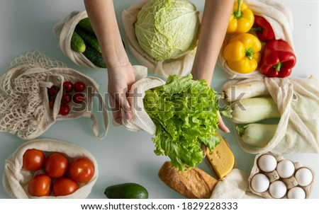 Photo of  Woman's hand, holding a reusable grocery bag with vegetables on a kitchen at home and takes salad out. Zero waste and plastic free concept. Mesh cotton shopper with vegetables. Ecology.