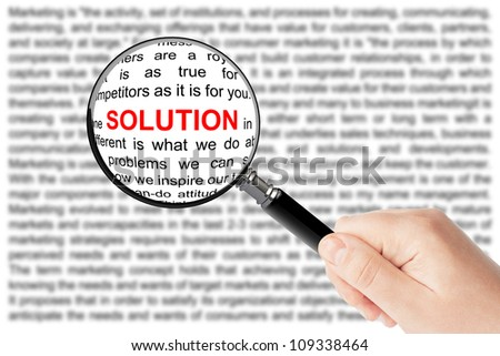 Woman's hand, holding classic styled magnifying glass, with Solution word