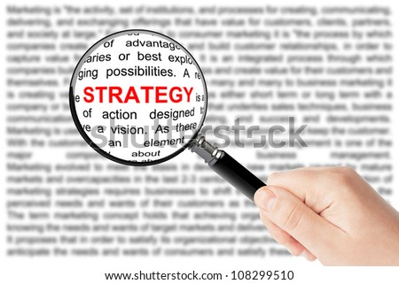 Woman's hand, holding classic styled magnifying glass, with strategy word