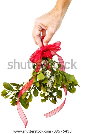 Woman's hand holding fresh green mistletoe with a red bow and ribbon on a white background