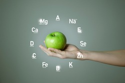 Woman`s hand holding green apple, microelement icons in clockface cirlce shape on grey background. Weight Loss concept template for product design.