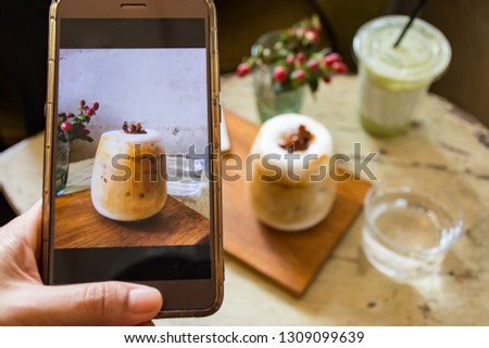 Woman's hand holding mobile phone with picture of ice coffee latte cup on screen and ice coffee latte cup on wooden plate blurred  background
