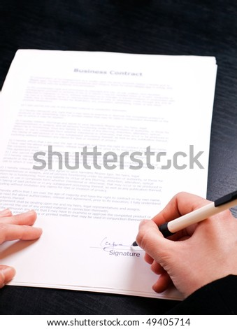 woman\'s hand holding pen and signing papers