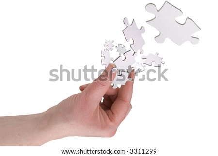 Woman's hand holding puzzle pieces between her fingers over a white background