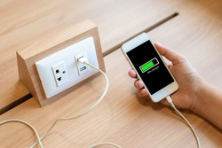Woman's hand holding smart phone and charging battery from built in usb socket on the table