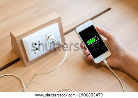 Woman's hand holding smart phone and charging battery from built in usb socket on the table Photo stock ©