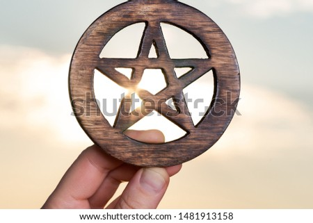 Woman's hand holding Wooden encircled Pentagram symbol at sunrise in front of the lake. Concept of Five elements: Earth, Water, Air, Fire, Spirit.