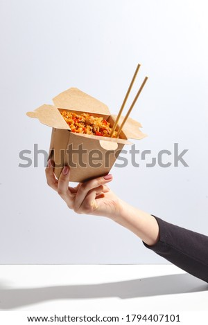 woman's hand holds a box of noodles. Asian cuisine
