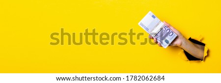 Woman's hand holds a bundle of five hundred euro bills on a yellow background. Banner.