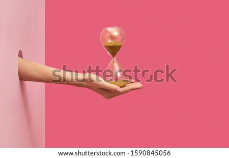 Woman's hand holds old hourglass in her hand through the hole in the wall on a duotone pink background with soft shadows, copy space.