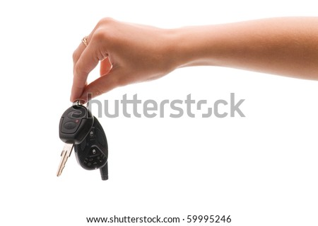 Woman's hand holds out key to the car. Isolated on white background.