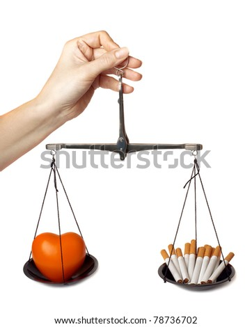 "Woman's hand holds the scales with orange heart and cigarettes isolated on white background. ""Concept - harm of smoking""."