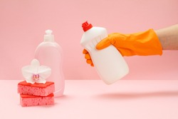 Woman's hand in a rubber protective glove with a bottle of dishwashing liquid on the pink background. Washing and cleaning concept.