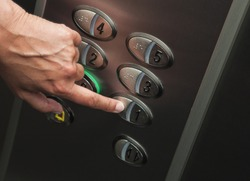Woman's hand is pressing the first floor in a elevator