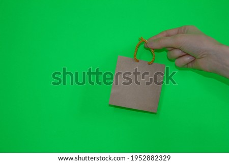 Woman's hand isolated on green background is holding mini shopping bag. Shopping concept. Space fot text. Stock fotó ©