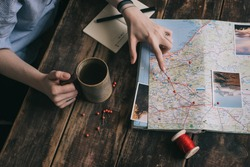 Woman's hand marks route on paper map of Europe using pins and red rope. Another hand holds cup of tea. Girl gets inspired with photos of nature and planning journey on dark wooden table