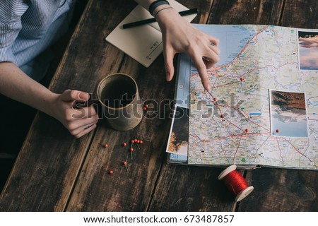 Woman's hand marks route on paper map of Europe using pins and red rope. Another hand holds cup of tea. Girl gets inspired with photos of nature and planning journey on dark wooden table - Shutterstock ID 673487857