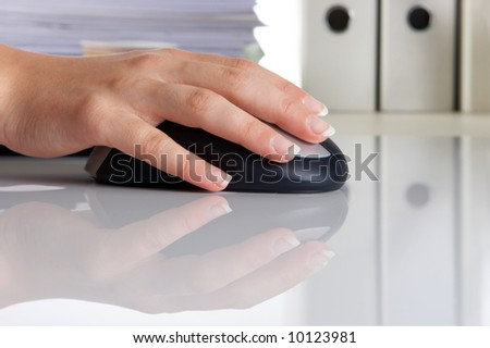 Woman's hand on a computer mouse, on a reflective surface