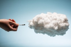 Woman's hand plugging a wire into a white cloud. Digital data storage. Cloud uploading.