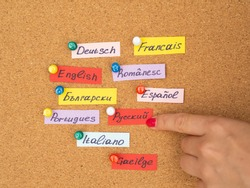 Woman's hand point to cards with different language names on a cork desk. Study foreign language concept