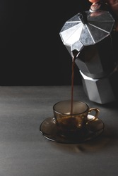 Woman's hand Pouring coffee from italian coffee maker in a brown glass pot, black background. Morning coffee