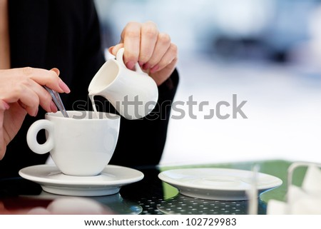 woman's hand pouring milk in white cup of coffee in outdoor cafe