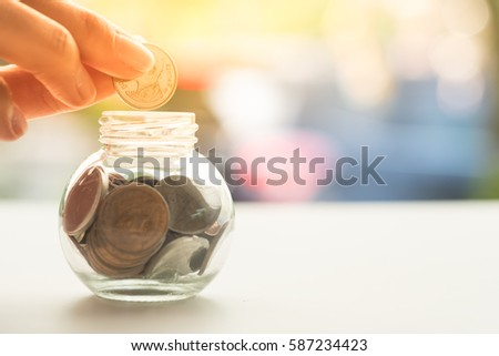 Woman's hand putting coin into glass of bottle for saving money and the wooden house as background. Concept for property ladder, mortgage and real estate investment . #587234423
