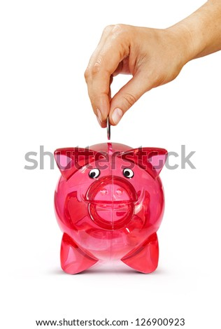 Woman's hand putting coin into piggy bank, isolated on white with path