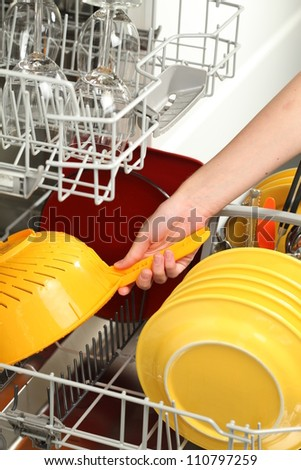 Woman's hand putting dirty dishes into dishwasher