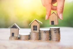Woman's hand putting house model on coins stack. Concept for property ladder, mortgage and real estate investment .