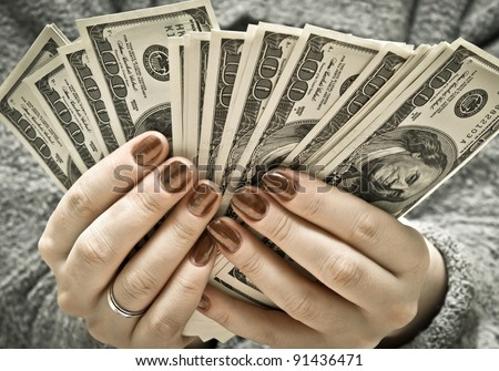 Woman's hand recount bundle of dollars