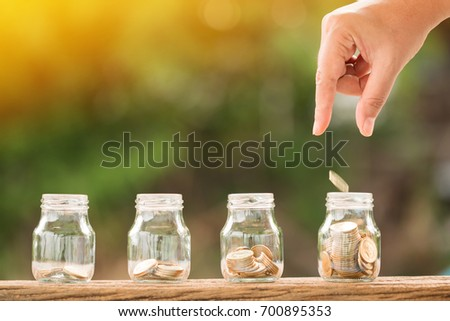 Woman's hand saves a coin in the bottle put on the wood in the morning sunlight, Business investment and saving growth money concept. #700895353