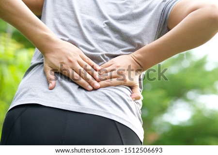 Woman's hand She is caught at the waist and her back is painful at the back in the park. Cause of the exercise. Photo stock ©