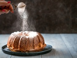 Woman's hand sprinkling icing sugar over fresh bundt cake. Powder sugar falls on fresh perfect bundt cake. Copy space for text. Ideas and recipes for breakfast or dessert