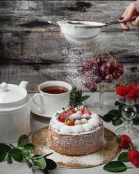 Woman's hand sprinkling icing sugar over fresh fruity cake. Powder sugar falls on fresh perfect fruity cake.