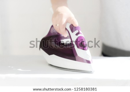 Woman's hand stroking the clothes steam iron on the background of the room. #1258180381